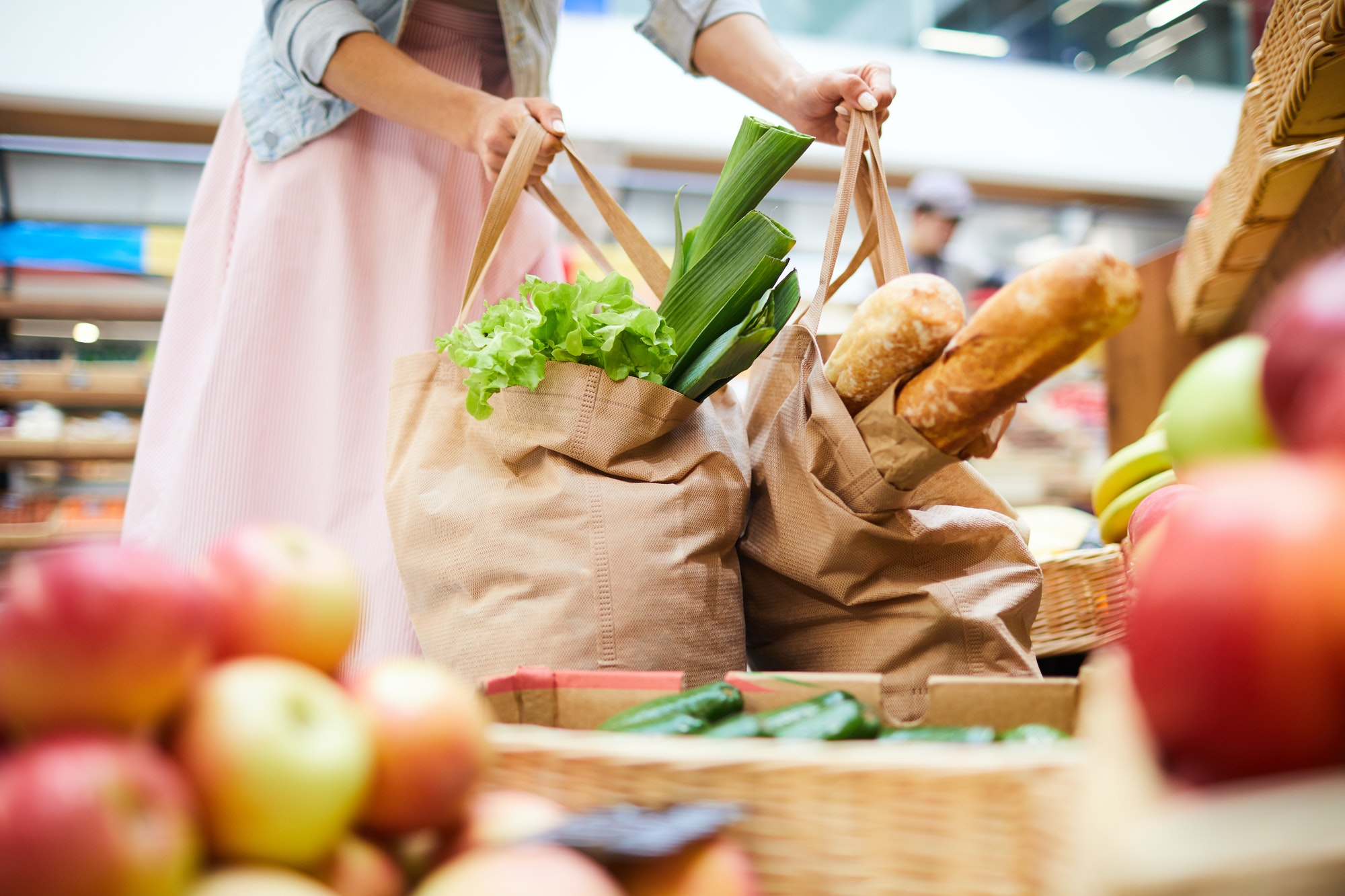 Woman picking heavy shopping bags in food store
