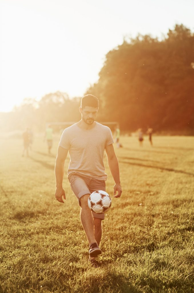 Man kick up the soccer ball. Training skills before he can show his own daughter how to do it